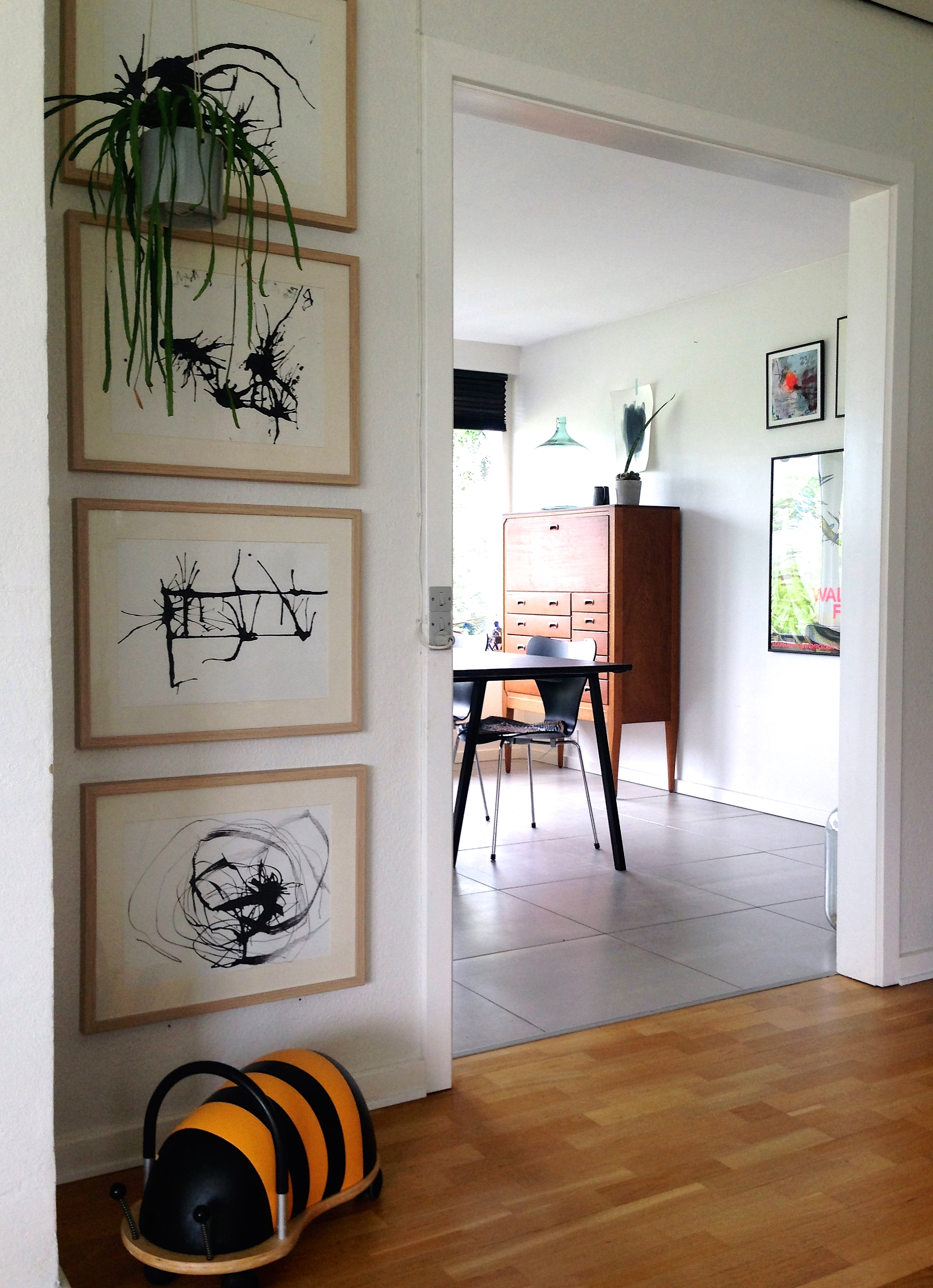 A view of the dining area from the family room. The boys Wheely Bug is ready for a ride! How great are the 4 pieces of original art? Each member of the family created their own masterpiece with paint and a straw. Simple modern frames create a unique collection.