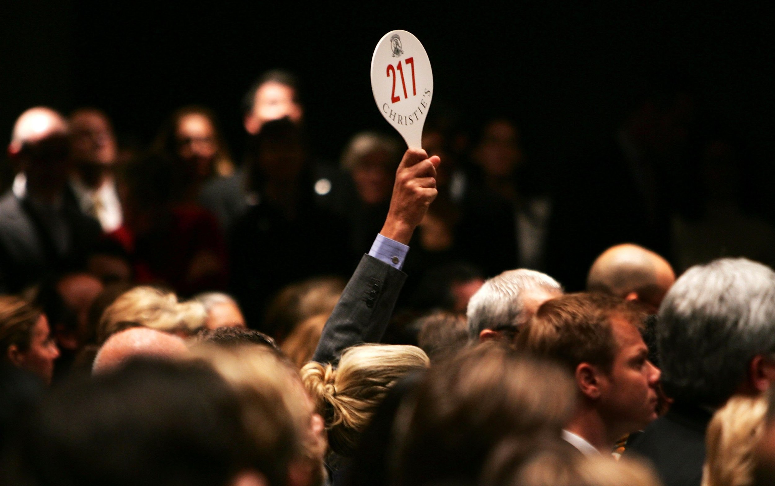 NEW YORK - NOVEMBER 15: A man holds his hand up while bidding on a work of art inside the auction house Christie's during the Post-War and contemporary Art sale November 15, 2006 in New York City. Christie's estimates that works by Warhol, Willem de Kooning, Roy Lichtenstein and others could go for up to $220 million in what the auction house says may be the most valuable post-World War II and contemporary art auction in history. Warhol's 'Mao' portrait from 1972 went for over 17 million, setting an all time record for the artist. (Photo by Spencer Platt/Getty Images)