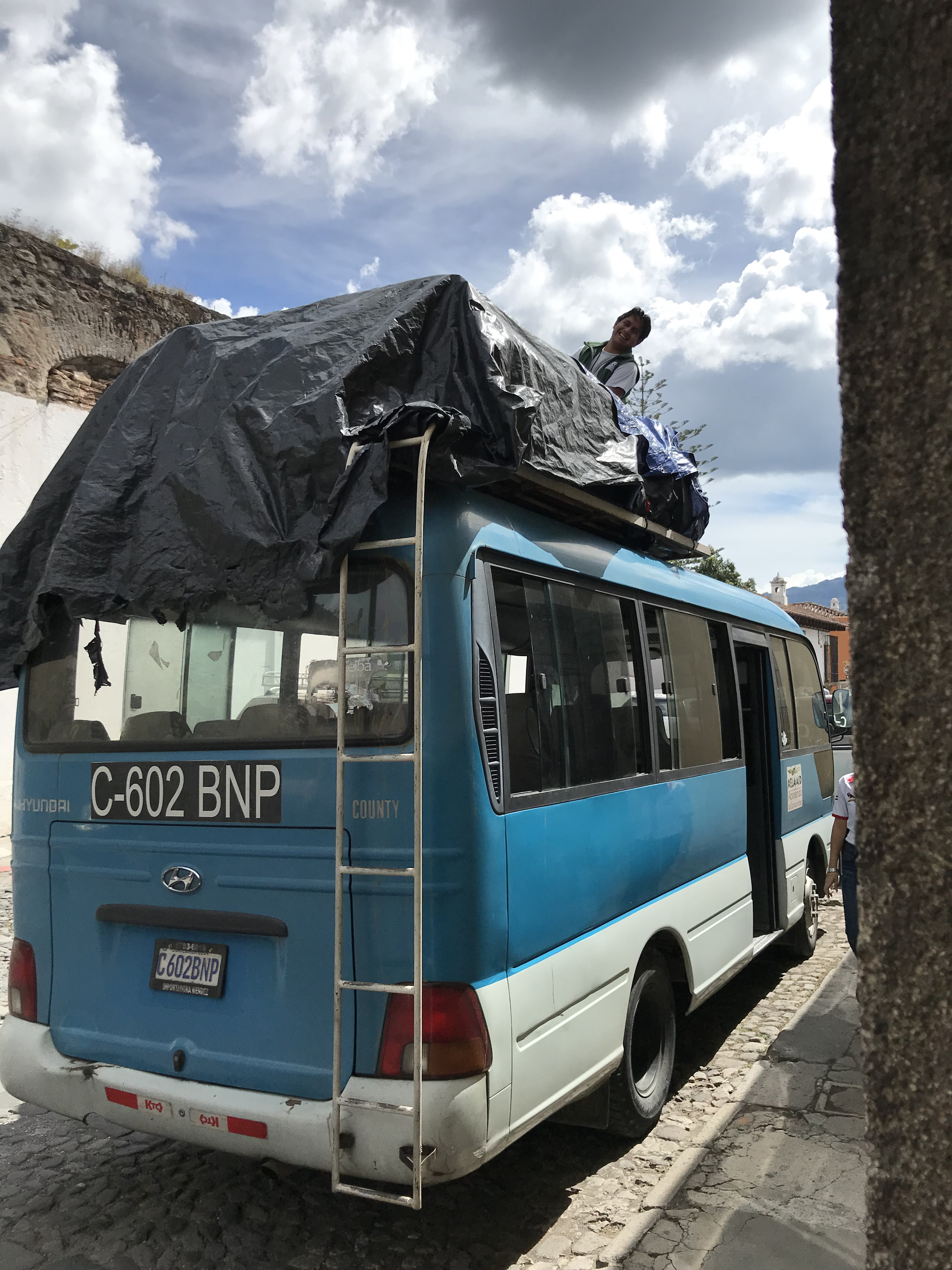 Our trusty driver, Carlos, loading luggage on top of our bus while Luis rounds us up and also drives a van for us.