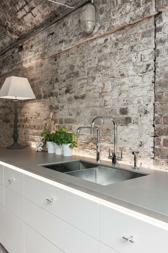 white modern kitchen with rough brick wall