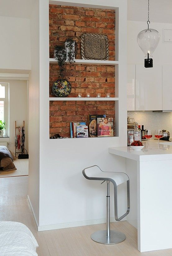 white kitchen with red brick wall