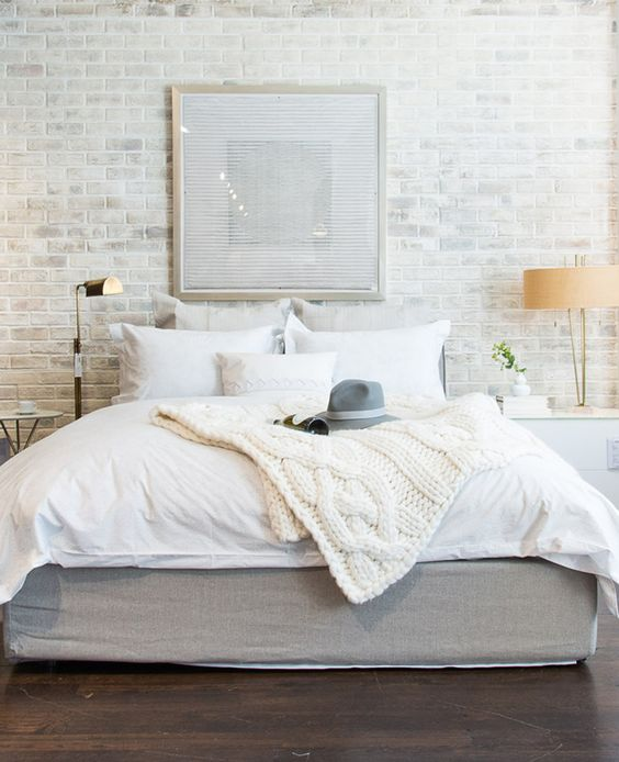 white bedroom with brick wall