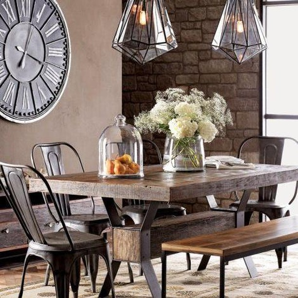 Sharp, edgy and strikingly stylish. The vintage charm of the large Roman clock and ancient stone wall is balanced with the sleek metal furniture and geometric pendant lights. Just add a bunch of blooms to soften the edges.  #RenoGuide #InteriorDesign #DiningRoom #CityLiving #Rustic #Geometric #Industrial #Inspo #DesignInspo