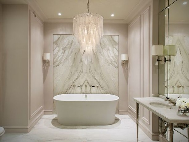Instantly upgrade your humdrum bathroom into a fabulous bath by adding a statement chandelier. This glass leaf chandelier effortlessly lights up the room! Its delicate details match the all-white opulence of the bathroom.  #RenoGuide #Bathroom #Chandelier #Lighting #BathroomGoals #BathroomInspo #Design #DesignInspo #InteriorDesign