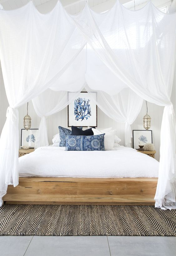 bed with white canopy curtains
