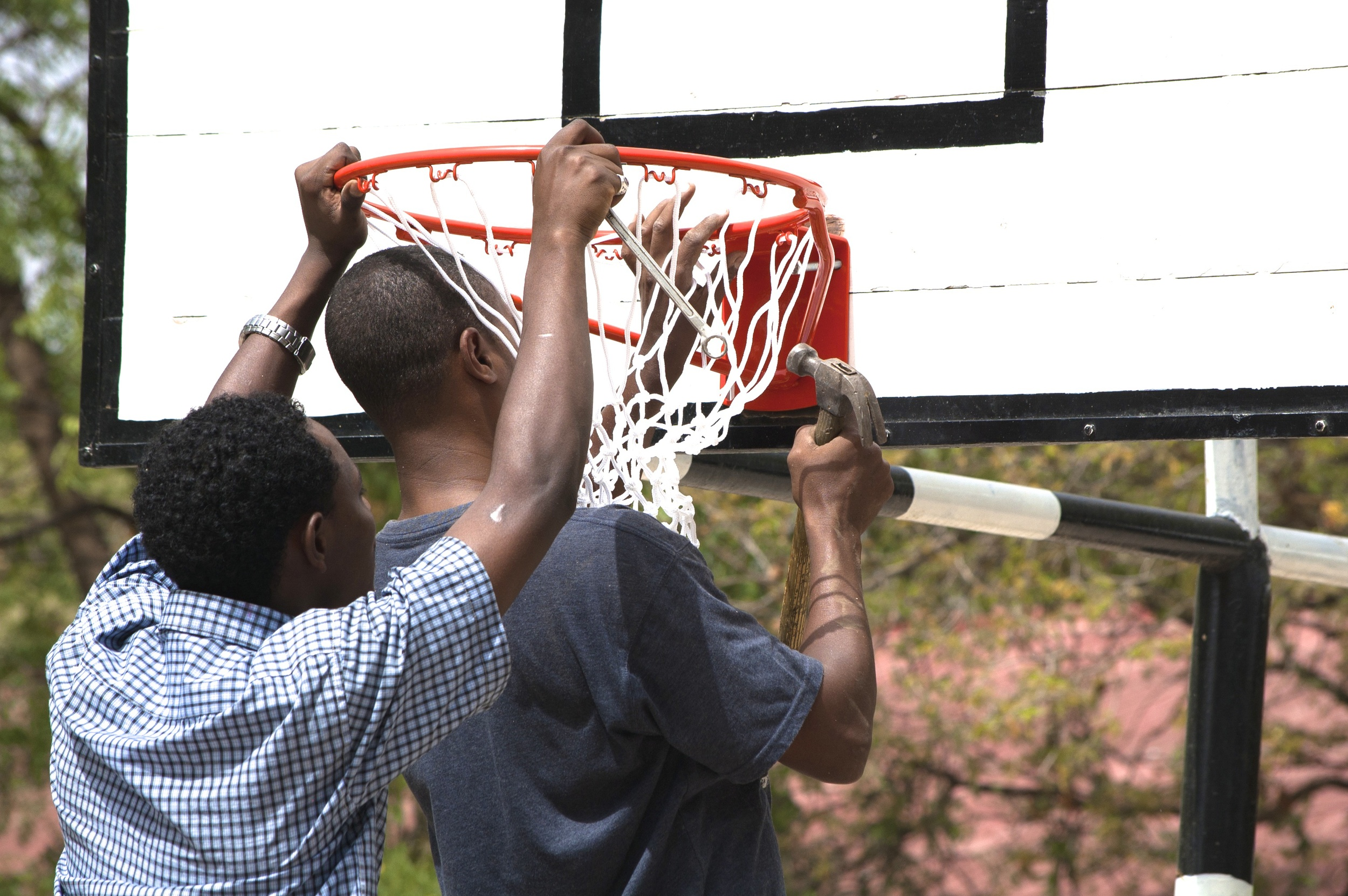 Putting up the new basketball rim and net.