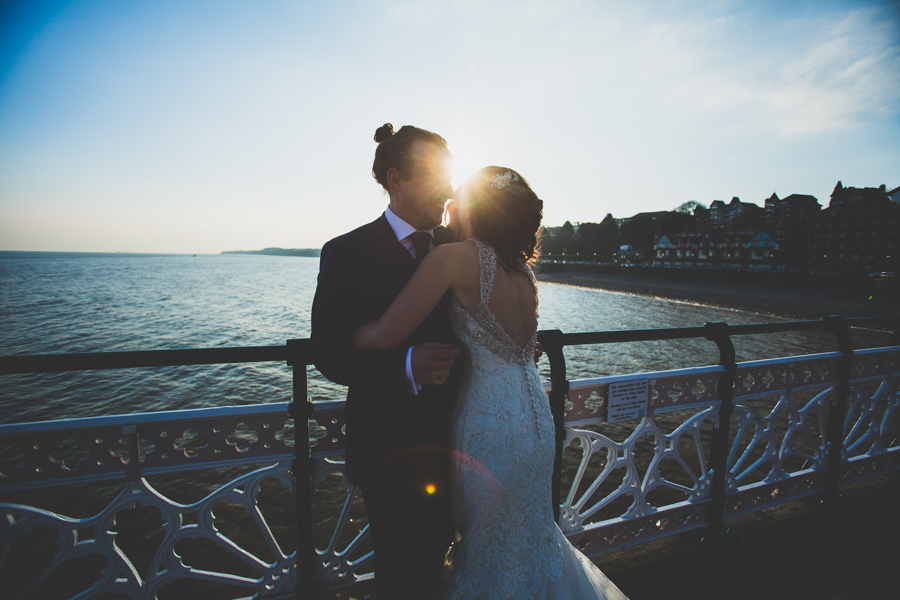 After just getting married the bride and groom enjoy a sunset on Penarth Pier South Wales