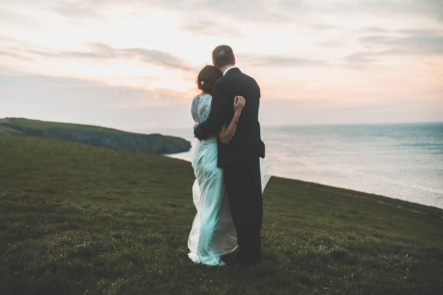 The bride and groom run off to witness the cornish sunset on their wedding day