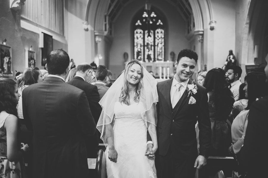 The Bride and Groom are smiling beautifully at the Church in Abergaveny Wales