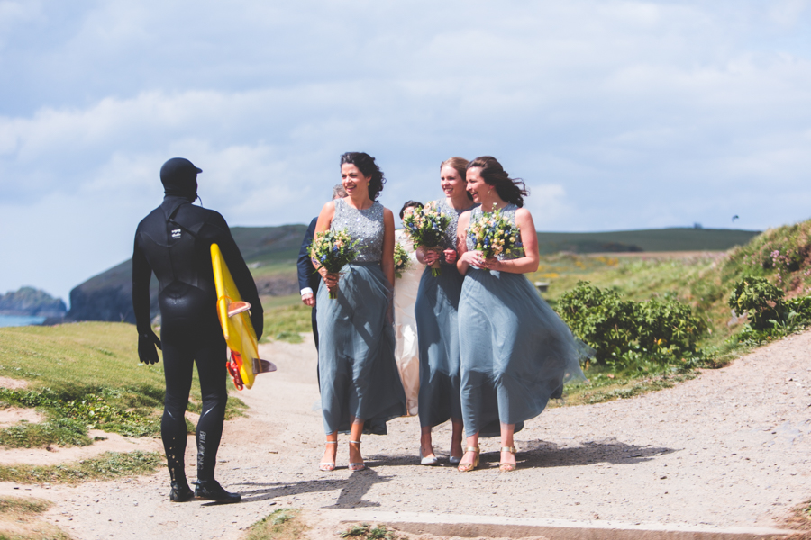 Three bridesmaids meet a surfer on the way to the beach ceromony in cornwall