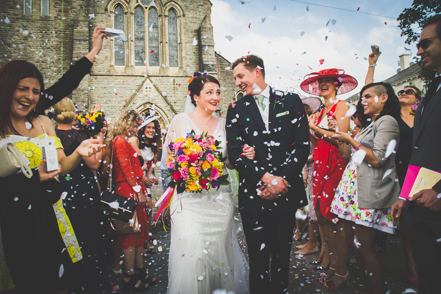 The Bride and Groom laughing whilst walking through the confetti in Bridgend