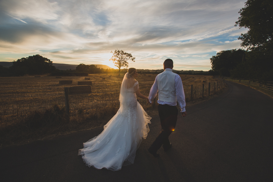 South Wales Wedding Photographers a couple walk into the sunset near Cwmbran