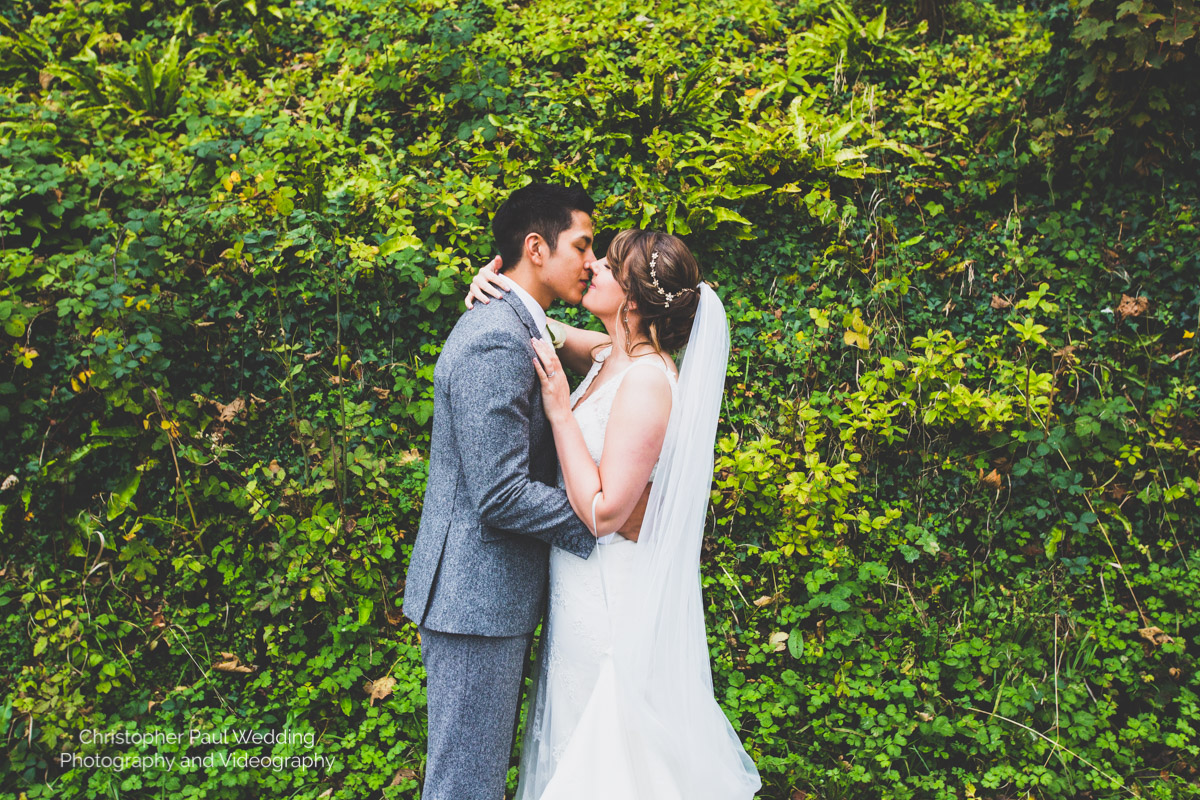A colourful wedding photo of a lush bride and groom at St Donat's