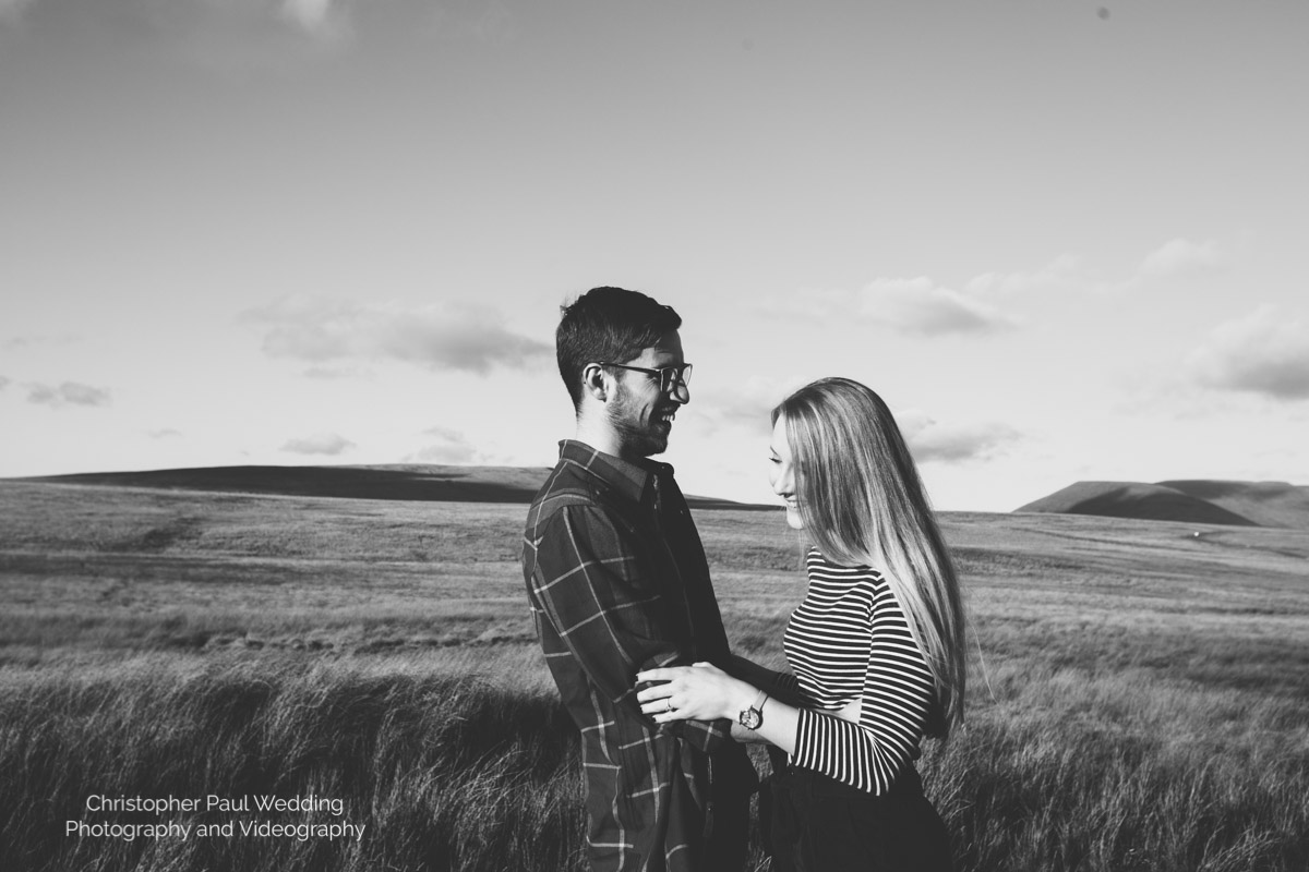 Lisa and Jack embracing each other in the beautiful Brecon Beacons. Two happy lovers are in the wilderness for their engagement photos.