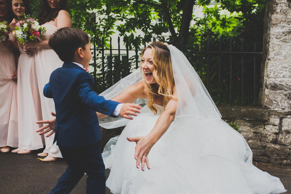 The Bride is crying with joy and hugs her ring bearer | Best South Wales Wedding Photographers