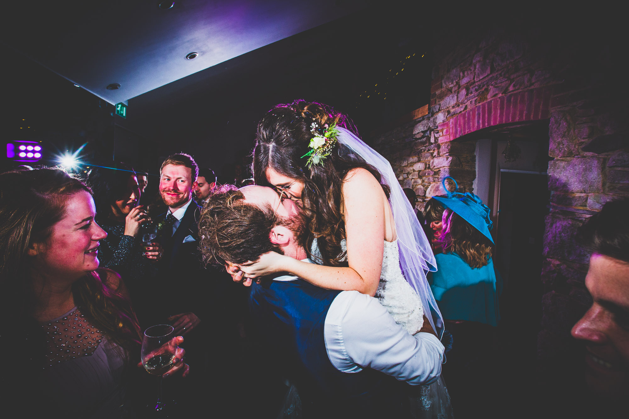 The bride and groom have an emotionally charged kiss on their wedding day
