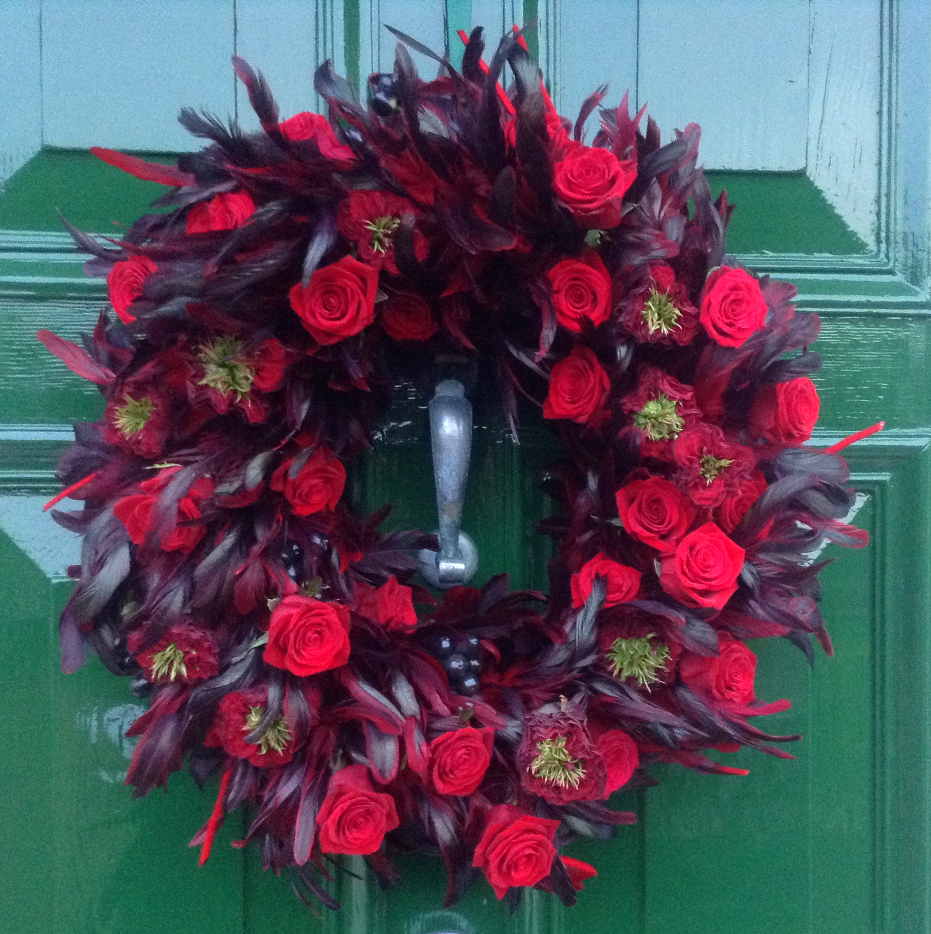 A Christmas wreath which featured on the front page of The Flower Arranger magazine and contained rich, darkest red feathers, red garden roses with green centres, traditional red roses and black berries.