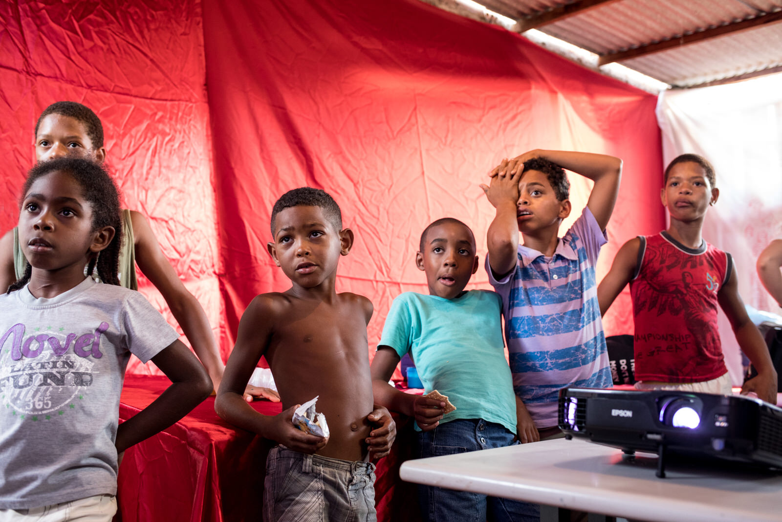 Children watching music videos projected on the walls of the community centre in Ocupação Guerreira Maria.