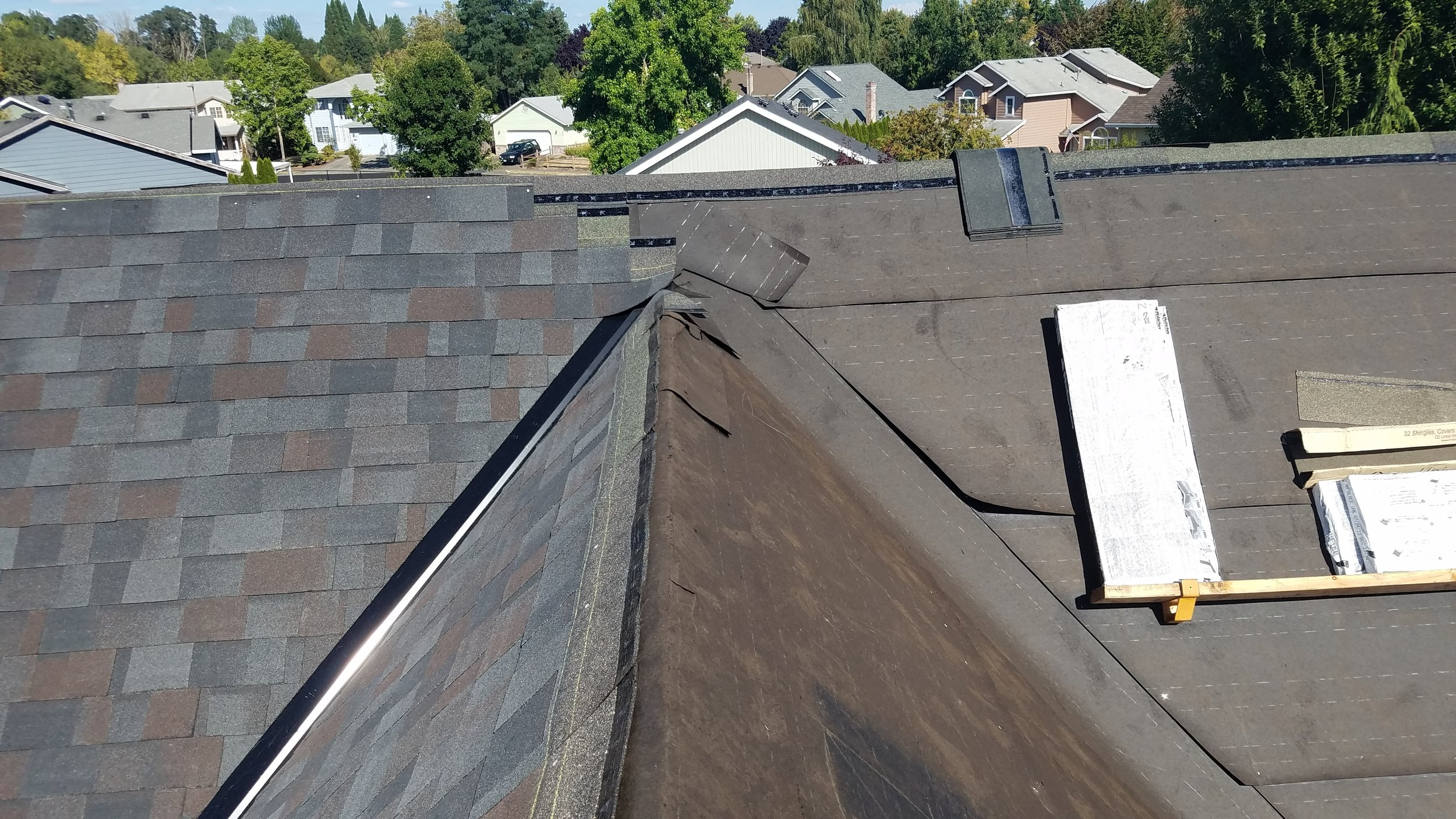 This photo shows part of the installation process with the felt underlayment, metal valley and laying the shingles down.