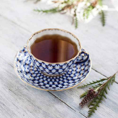A cup of Lapsang Souchong next to a pine cone