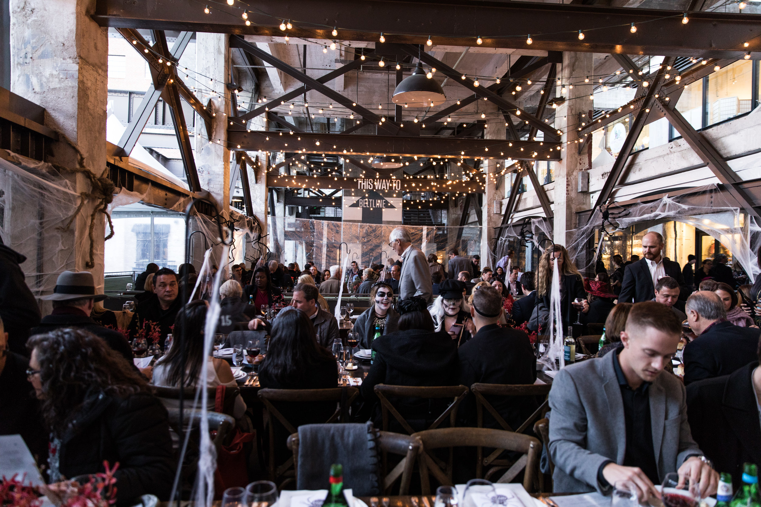 Guests at dining tables under the Ponce City Market train trestle