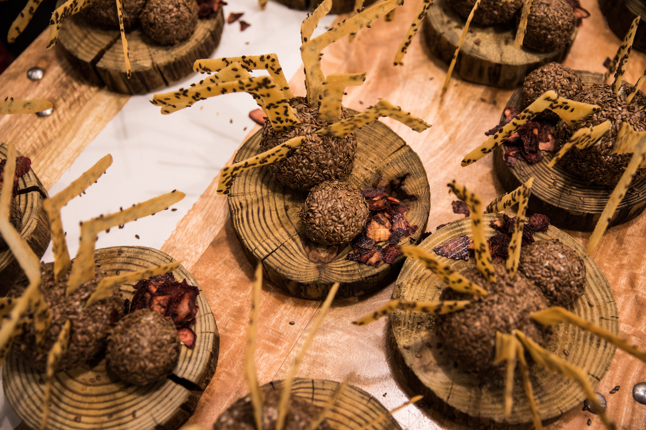 Plates of food on a tabletop, made to look like large spiders, in keeping with the event's macabre theme