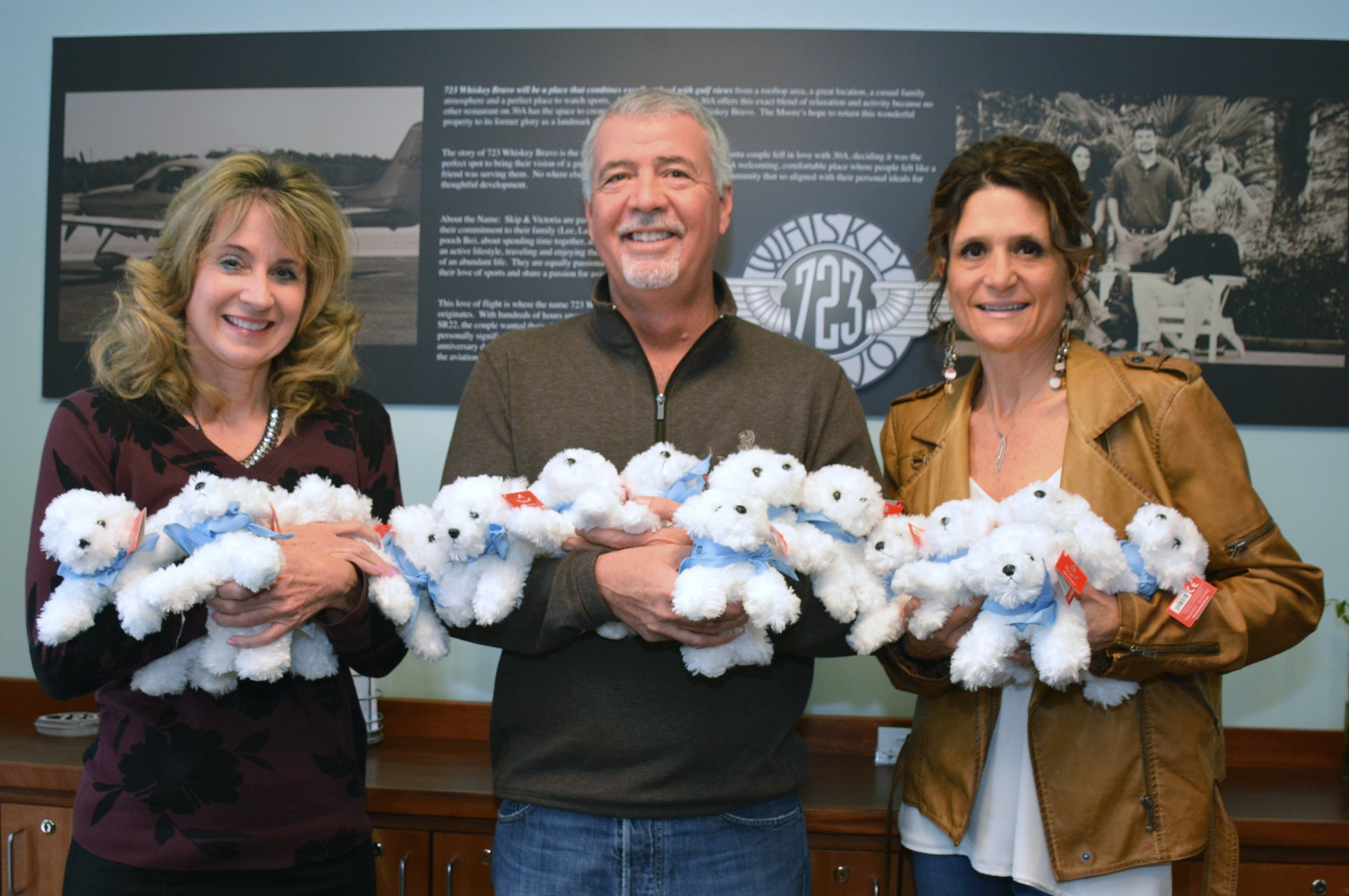 Benefitting ECCAC, the staff at 723 Whiskey Bravo restaurant in Seagrove Beach have successfully raised $44,869 in donations for stuffed animal Riley therapy dogs in the past three years. Pictured are ECCAC CEO, Julie Hurst-Porterfield and owners Skip and Victoria Moore.