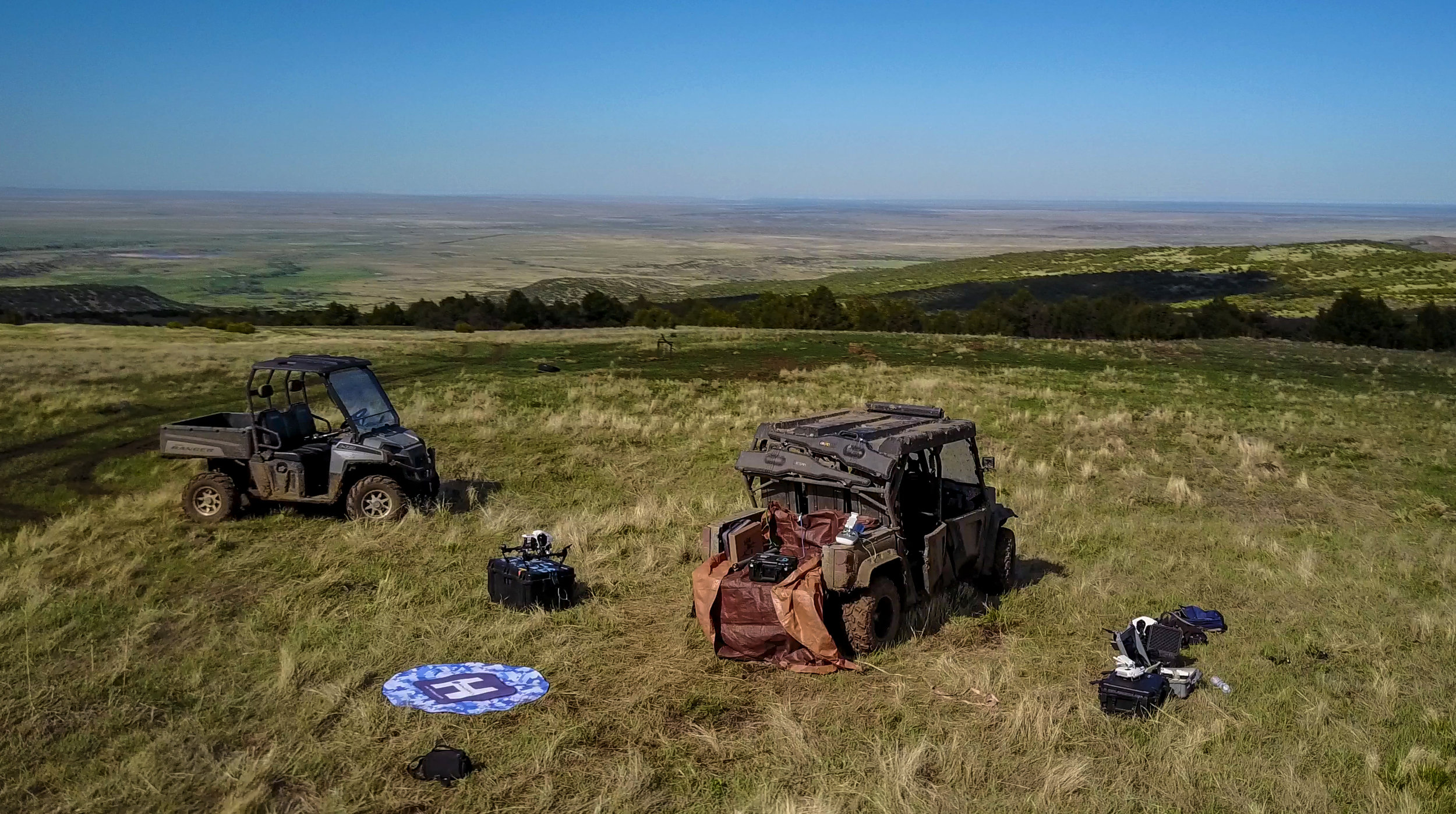 Designated takeoff area with a helipad, GPC cases, UTV's and two Inspire 1's while conducting a water density mapping mission.