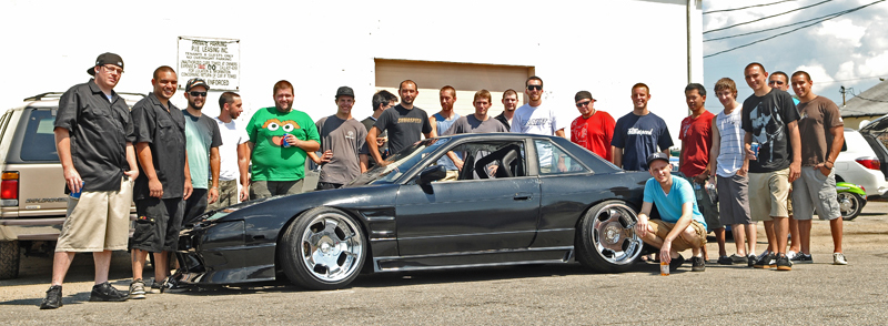 Stephen James with his 240sx, built by the rest of Sumospeed, most of which pictured behind the car.