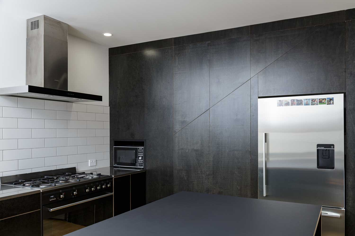 Black plywood kitchen wall and bench