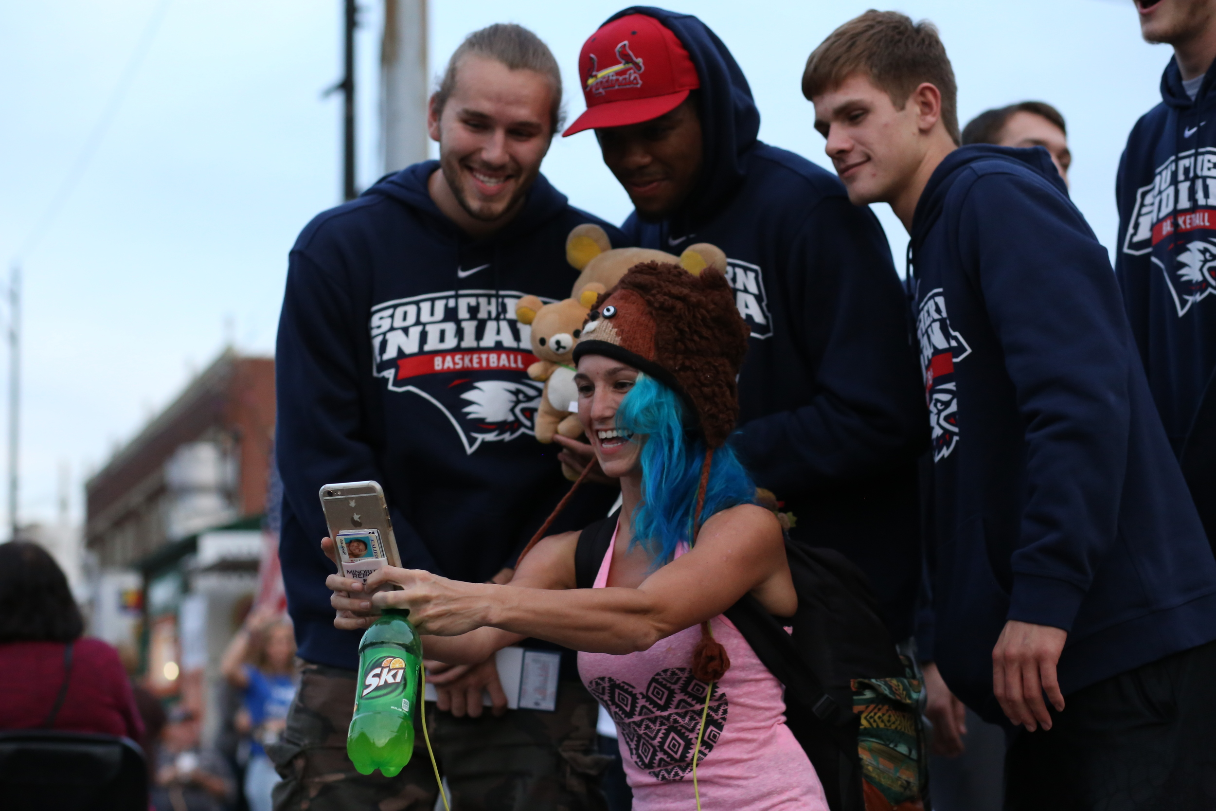 "Alex Bigge (front), a fan visiting from Los Angeles, California, poses for a selfie with team members Shane Seniour (left), a senior forward, Terrence Tisdell (middle), a junior forward and Alex Stein (right) a freshman guard at the West Side Nut Club Fall Festival in October of 2015. Bigge's brother is a student at USI and she said, ""Im only in town a couple times a year, so I had to get a picture with the boys."" (Shot for The Shield)"