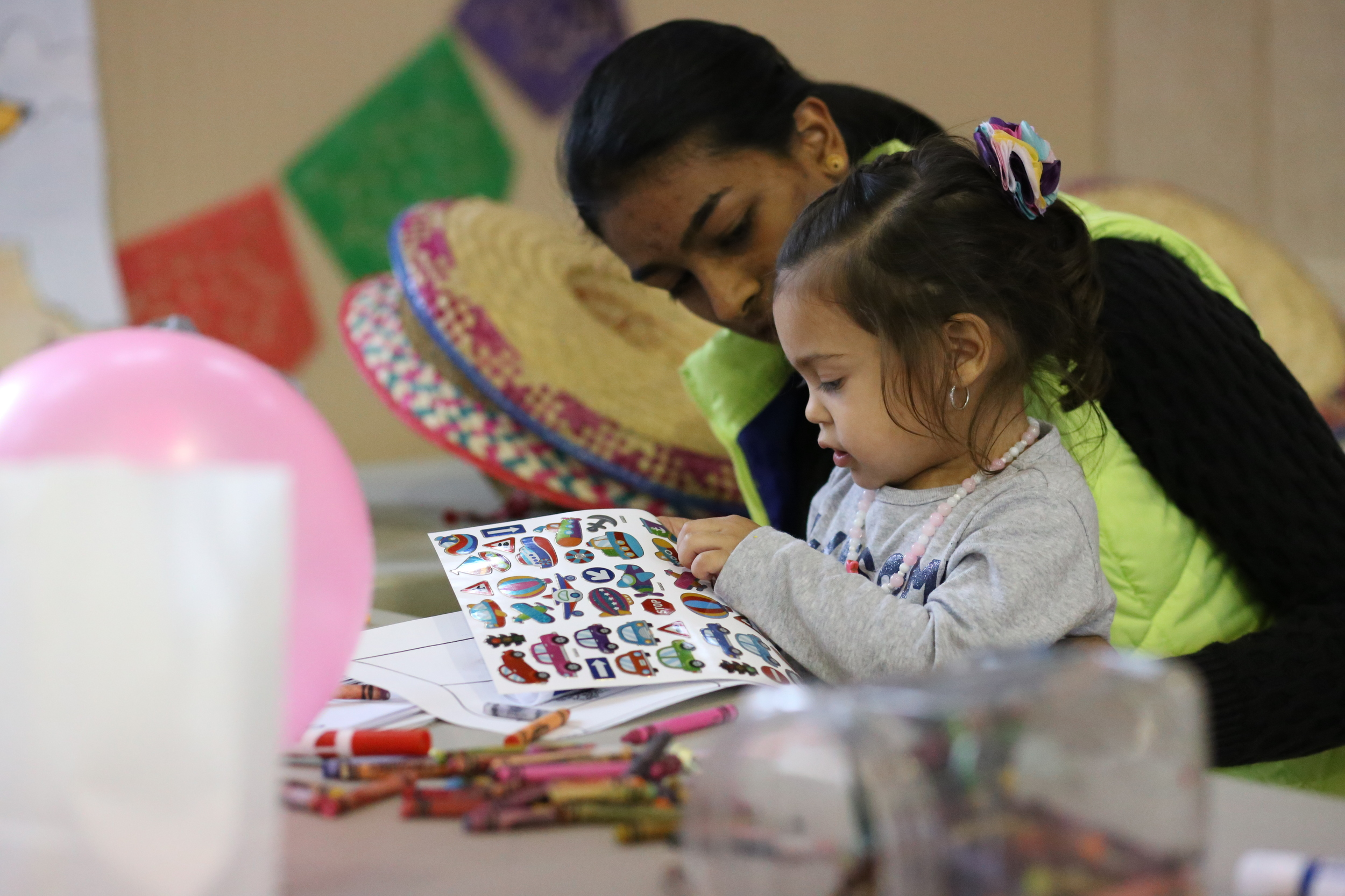 Two-year-old Alyson Sanchez picks out a sticker with help from 15-year-old Signature School student Maansi Asthana at a craft station during Global Crossroads in New Harmony November of 2015. Global Crossroads was a daylong culture and musical festival filled with Latin food, music and art as well as a performance by the first in New York all women's mariachi band, Mariachi Flor de Toloache. (Shot for The Shield)