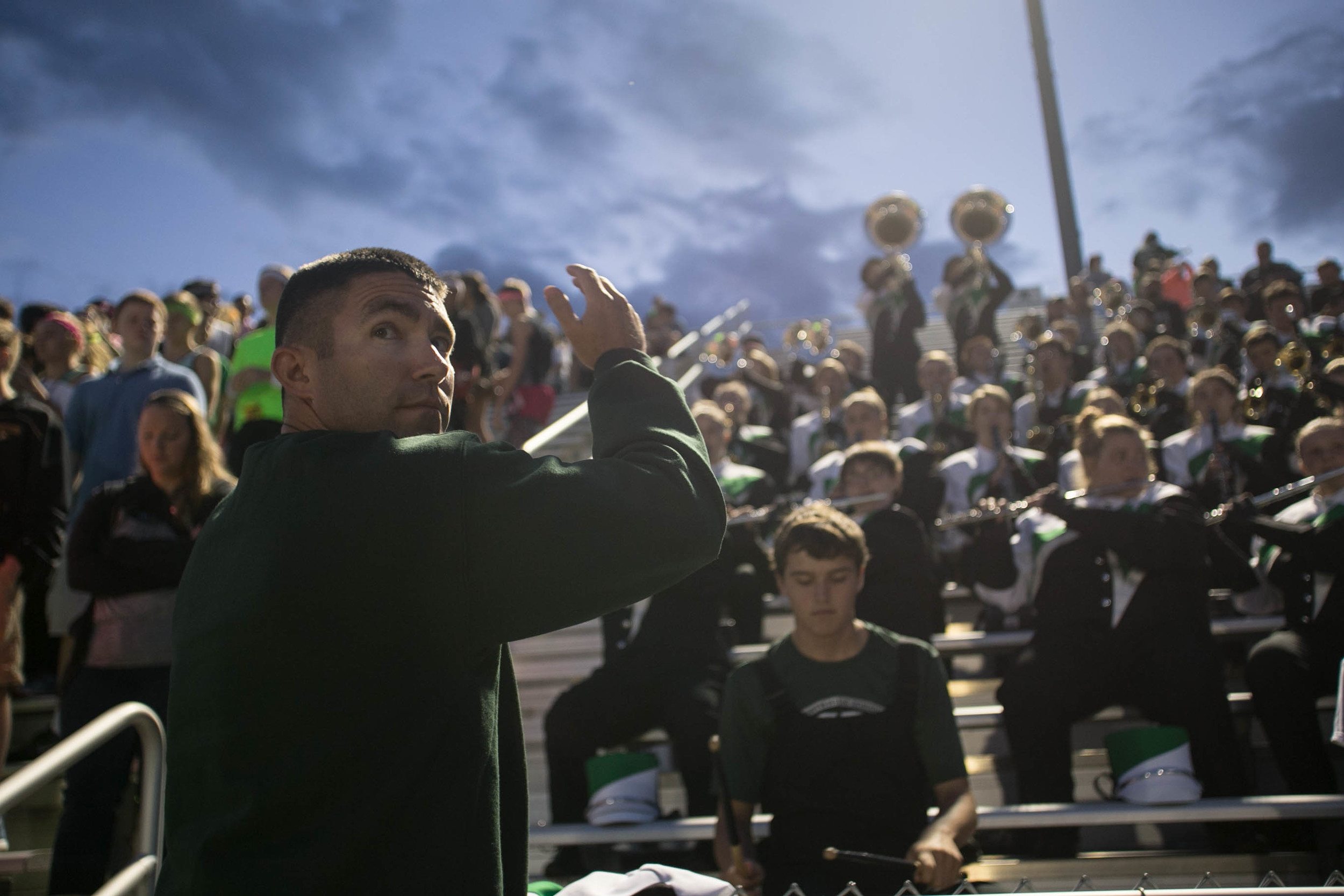 Band director Jay Emmert looks to the scoreboard as he direct's North High School's band during a football game in September of 2015. (Shot for Evansville Courier & Press)