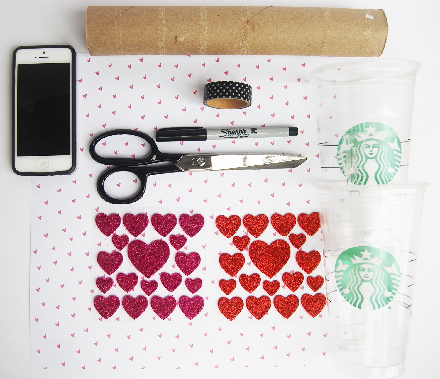 All The Supplies You Will Need To Make Your Valentine Say Anything: paper towel roll, tape, scissors,  sheet of decorative paper or printer paper, a smart phone, 2 disposable cups, a Sharpie® pen and sticker glitter hearts.