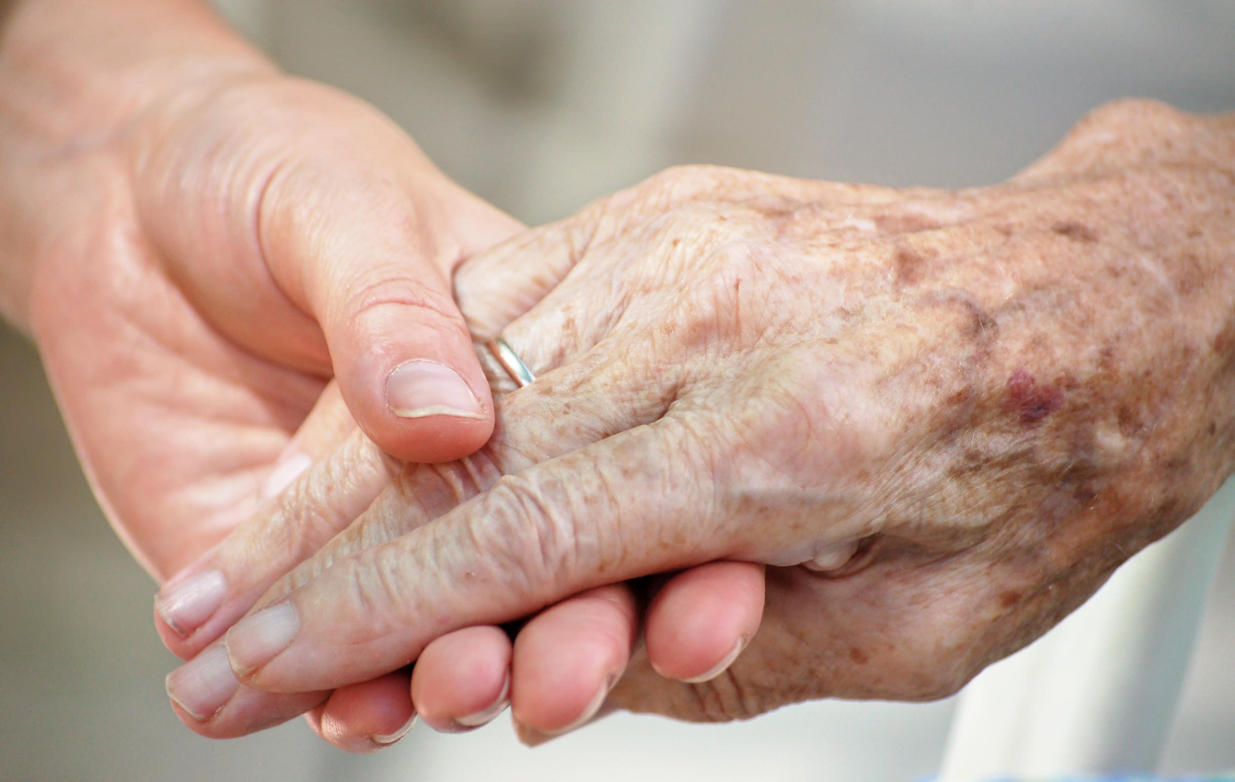 elderly holding hands