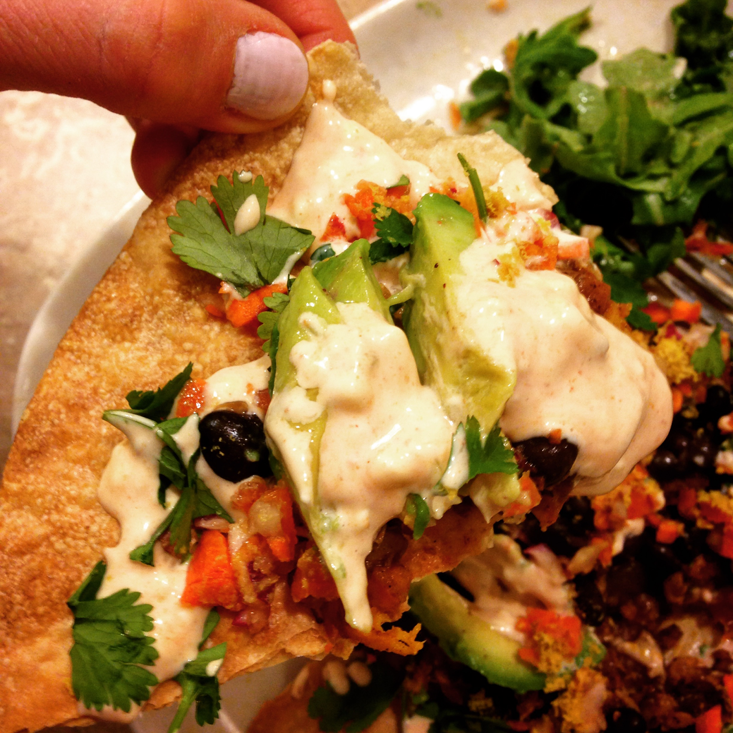 vegetarian and vegan tempeh tostada with black beans, cilantro, and spicy mayo