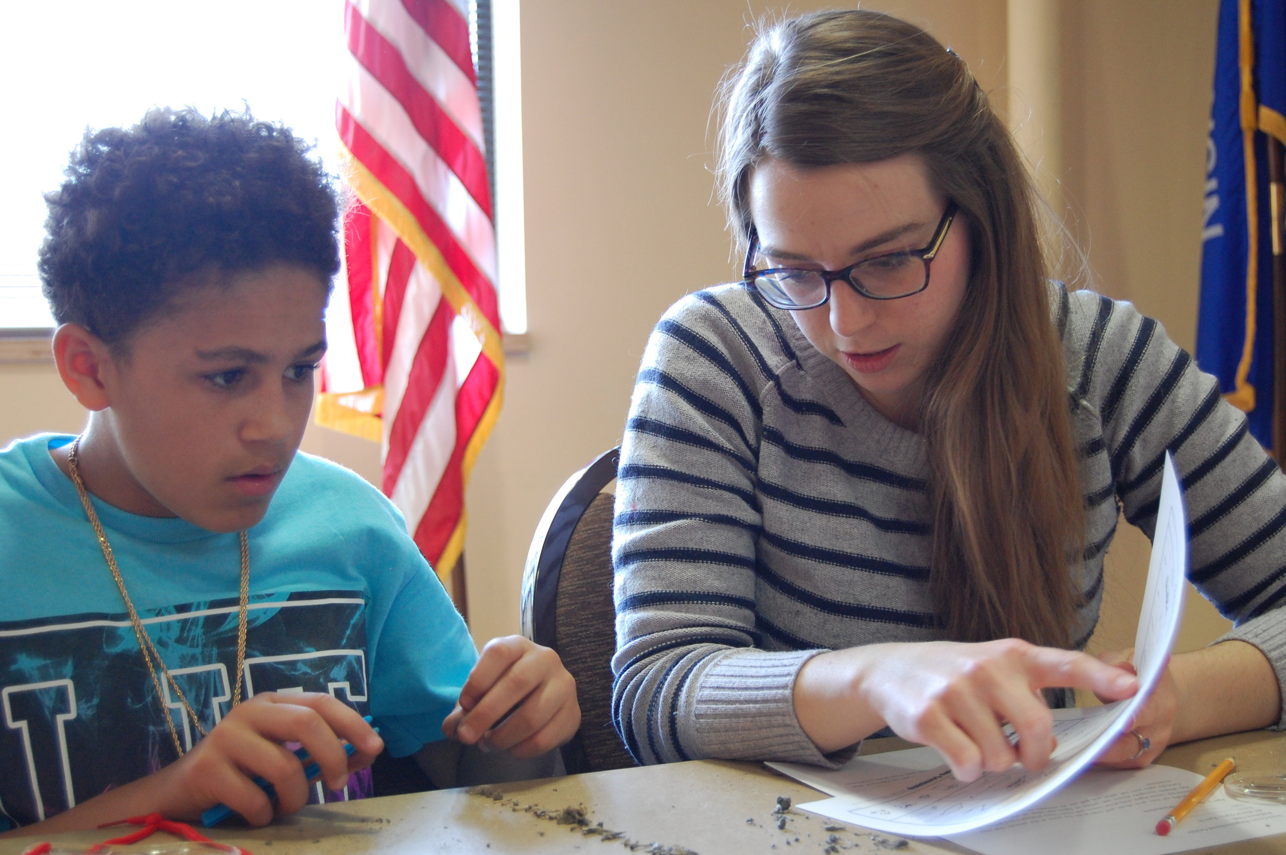 Education intern, Olivia, helps a student ID mammal bones found in an owl pellet (Vera Court)
