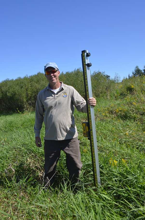 Kurt Waterstad posing with the laser elevation reader. Photo by Mark Martin.