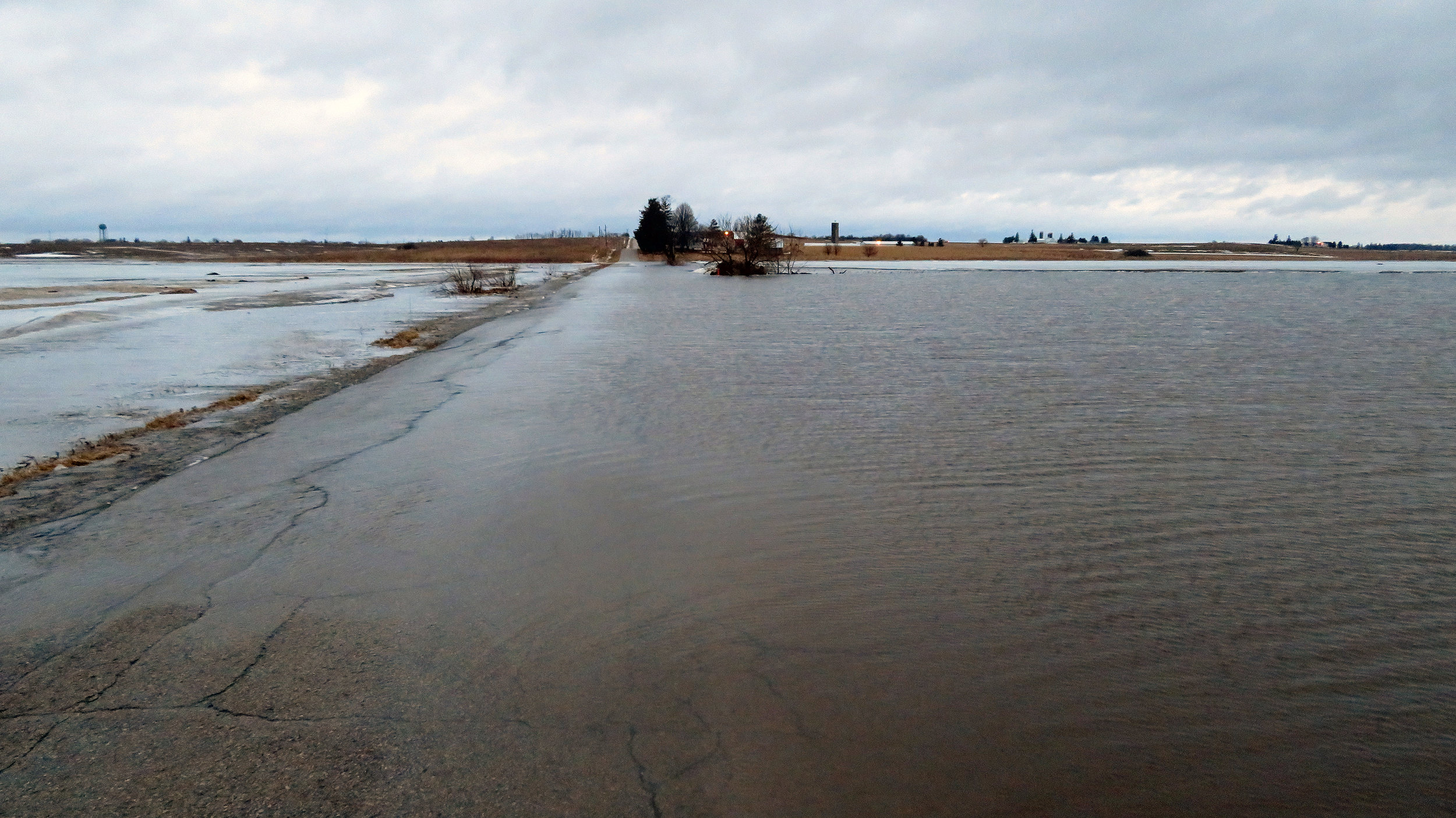 Above: Goose Pond Road (looking north towards Arlington).  The road is covered by up to three inches of water for almost 1,000 feet. The dark mound to the right (east) of Goose Pond Road is the rock pile. The pull off next to the rock pile is where many people bird watch from the Goose Pond Road causeway, and it is completely flooded.