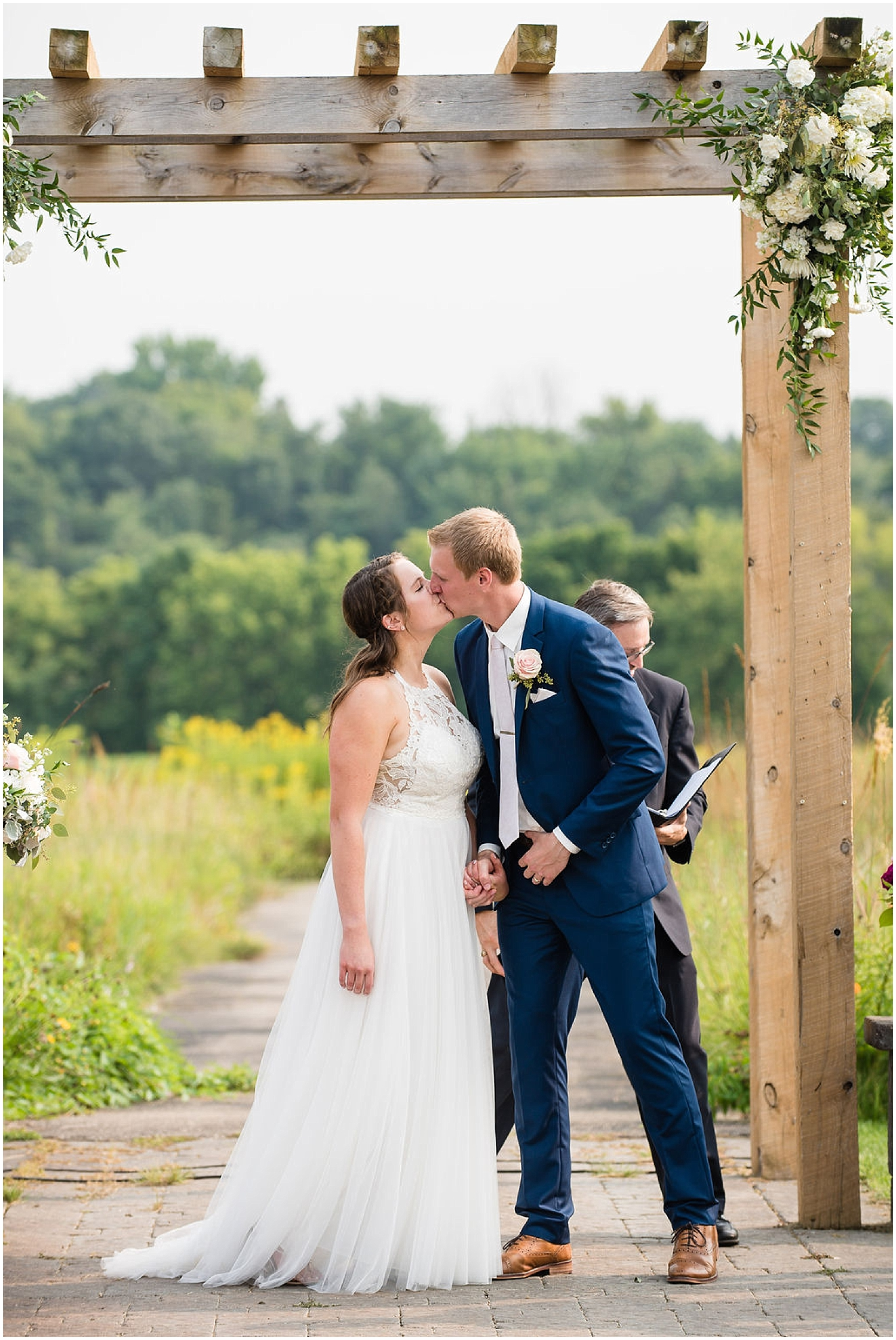 bride and groom kiss at their outdoor wedding ceremony