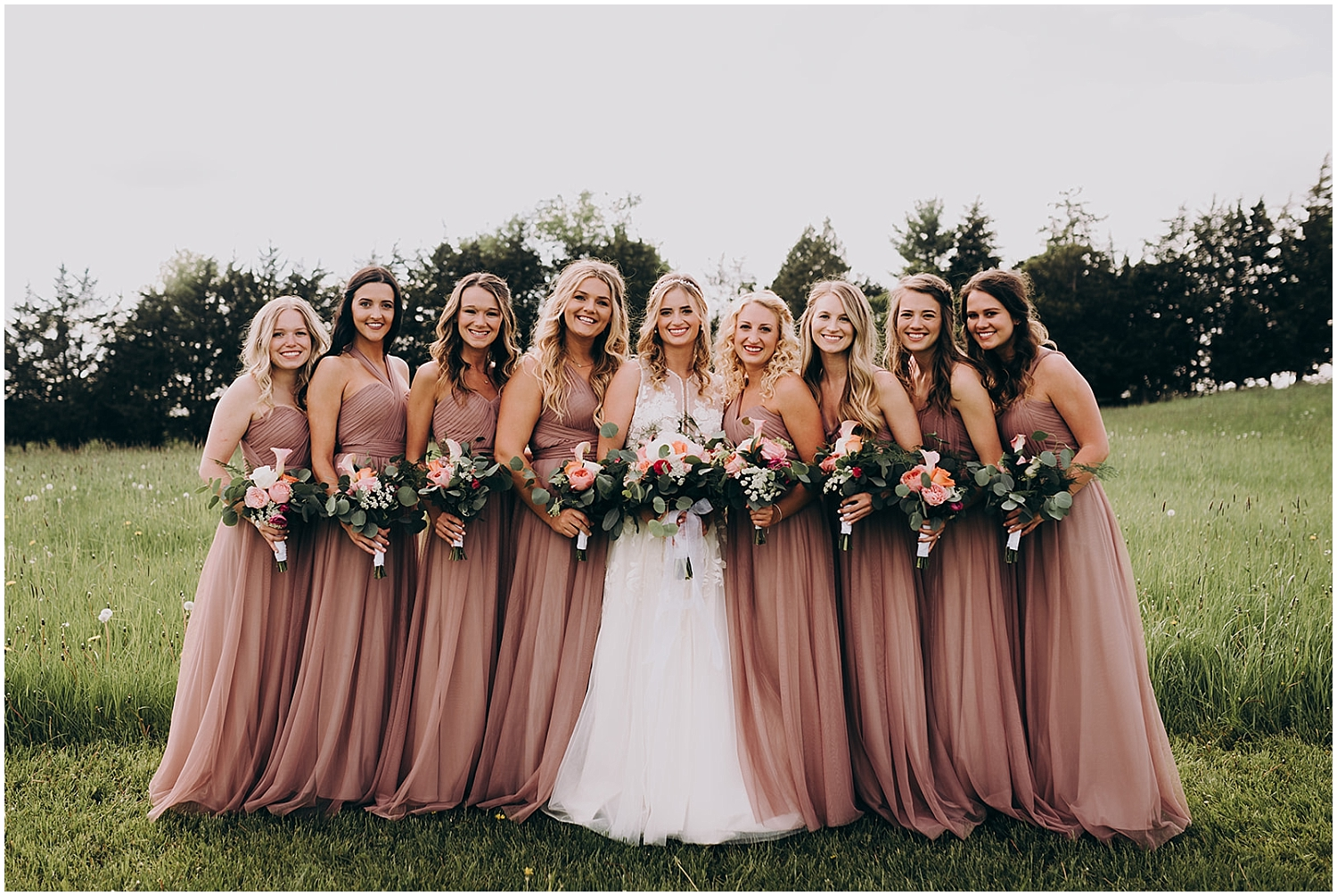 the bride and bridesmaids holding their wedding bouquets