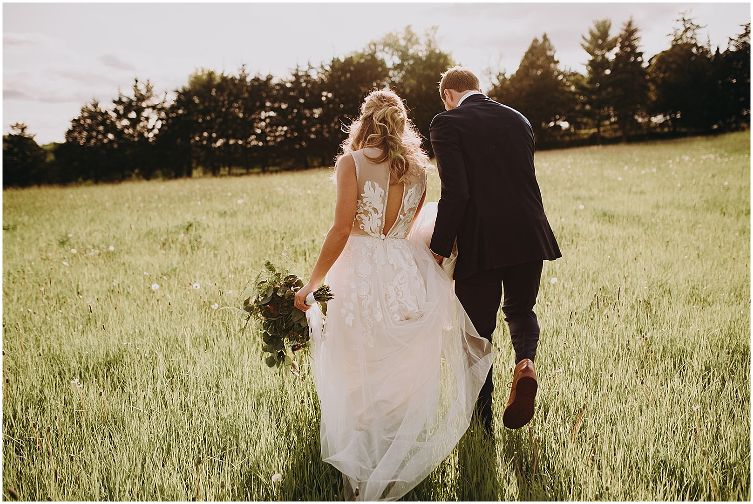 the bride and groom holding hands in the field