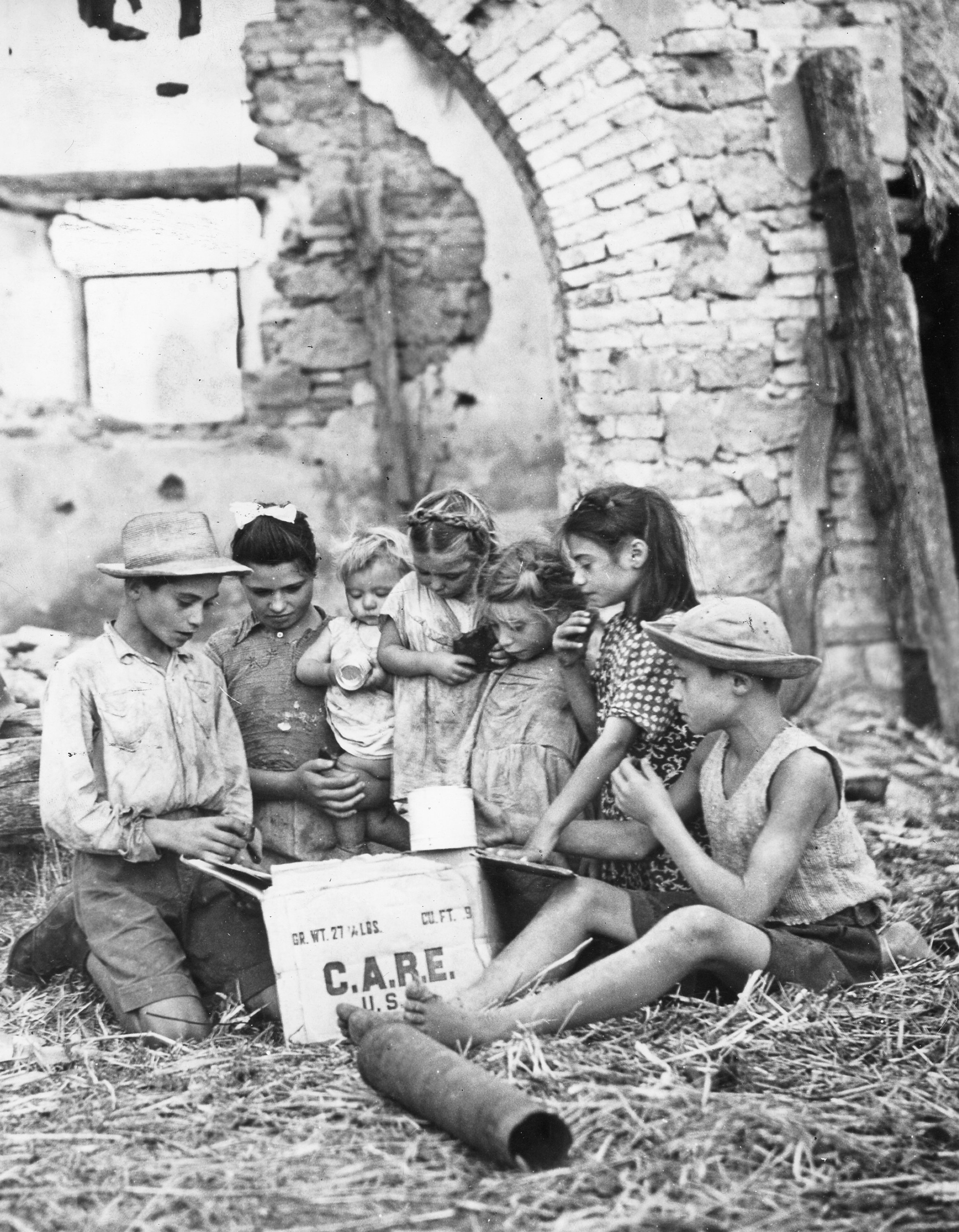 In the ruins of their farmhouse near Cisterna, Italy, these children of the Zuccairi family delve into the contents of a big CARE food package from America. During the Nazi occupation, the family lived in the caves near Cisterna.