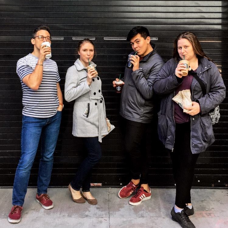 Four young adults posing against a black garage door sipping on Starbucks Coffee beverages.
