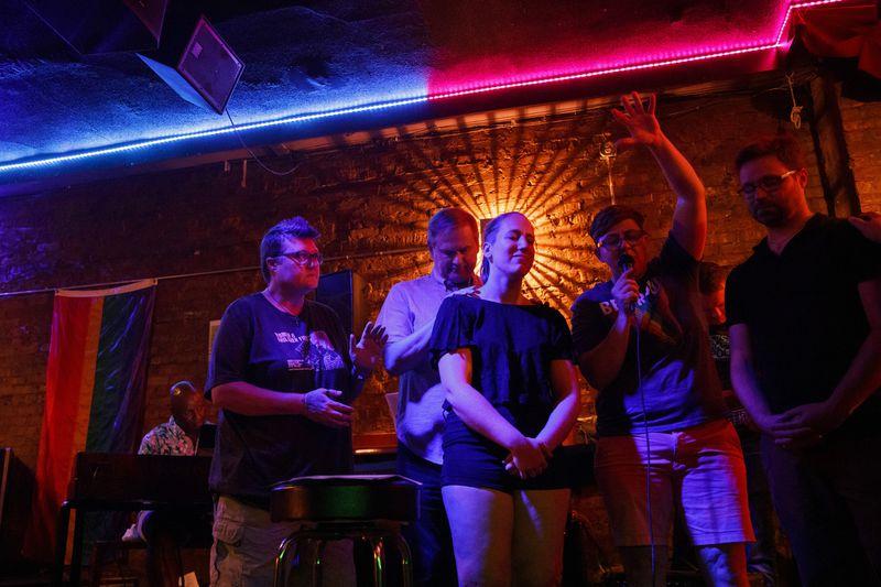 Kelli Harrison, from left, Bob Niehaus, Kelly Ravenscraft, Jennie Garcia, and Alex Aivars, pray during the Affirming Worship service at Atmosphere Bar on Aug. 13, 2019, in Chicago. (Armando L. Sanchez / Chicago Tribune)