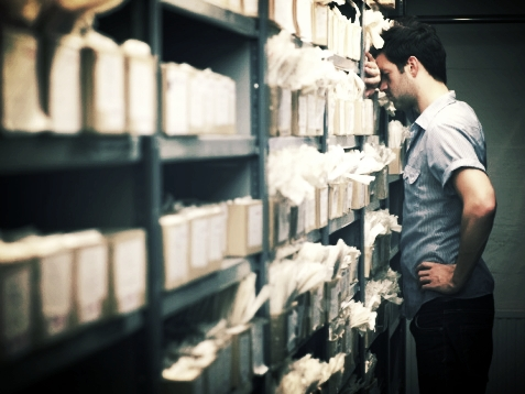Upravljalec se prebija čez množico razpršene in neurejene dokumentacija.