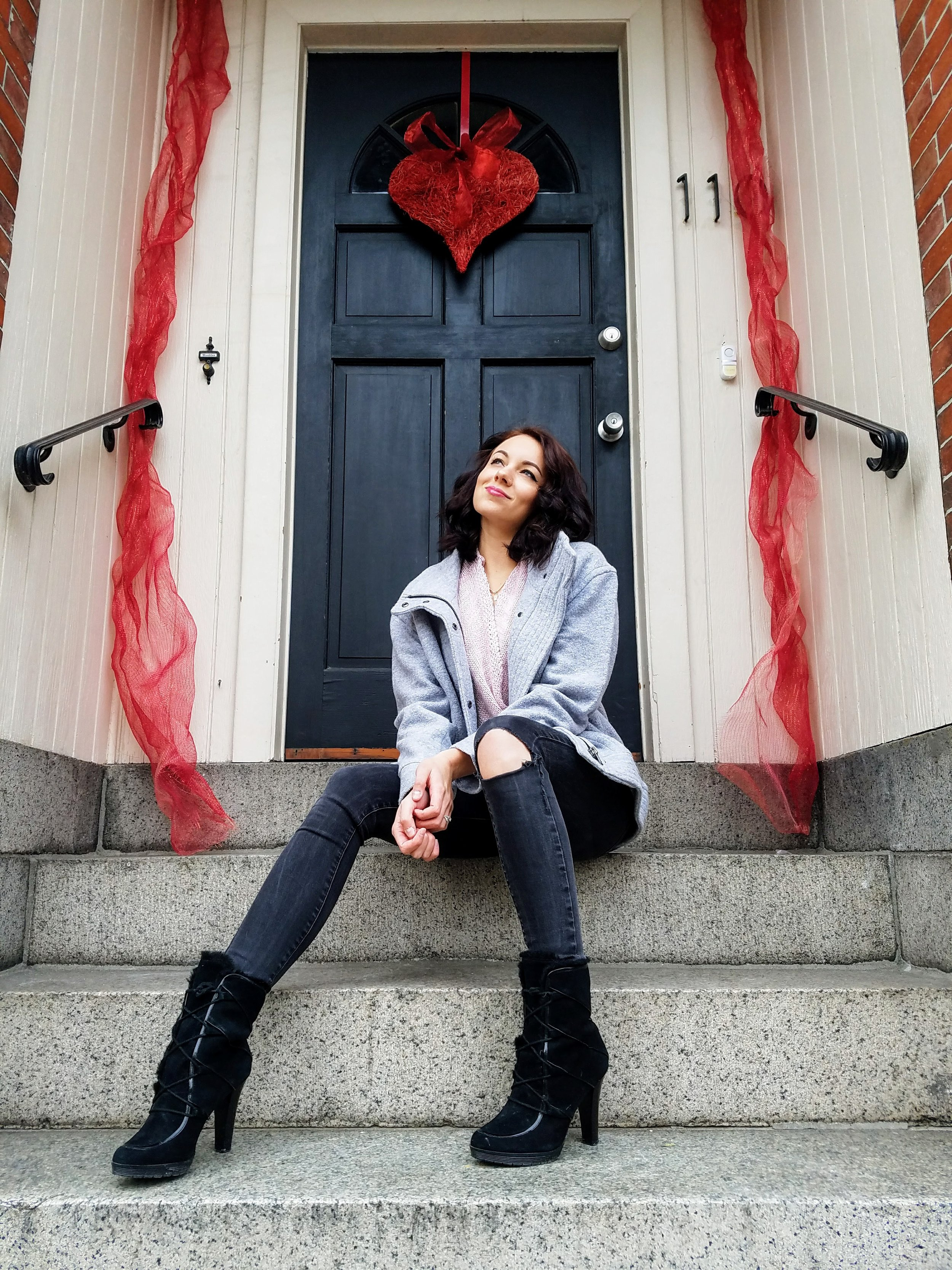 A girl on the the steps. Gray jacket, black booties, and ripped jeans. Valentine's Day.