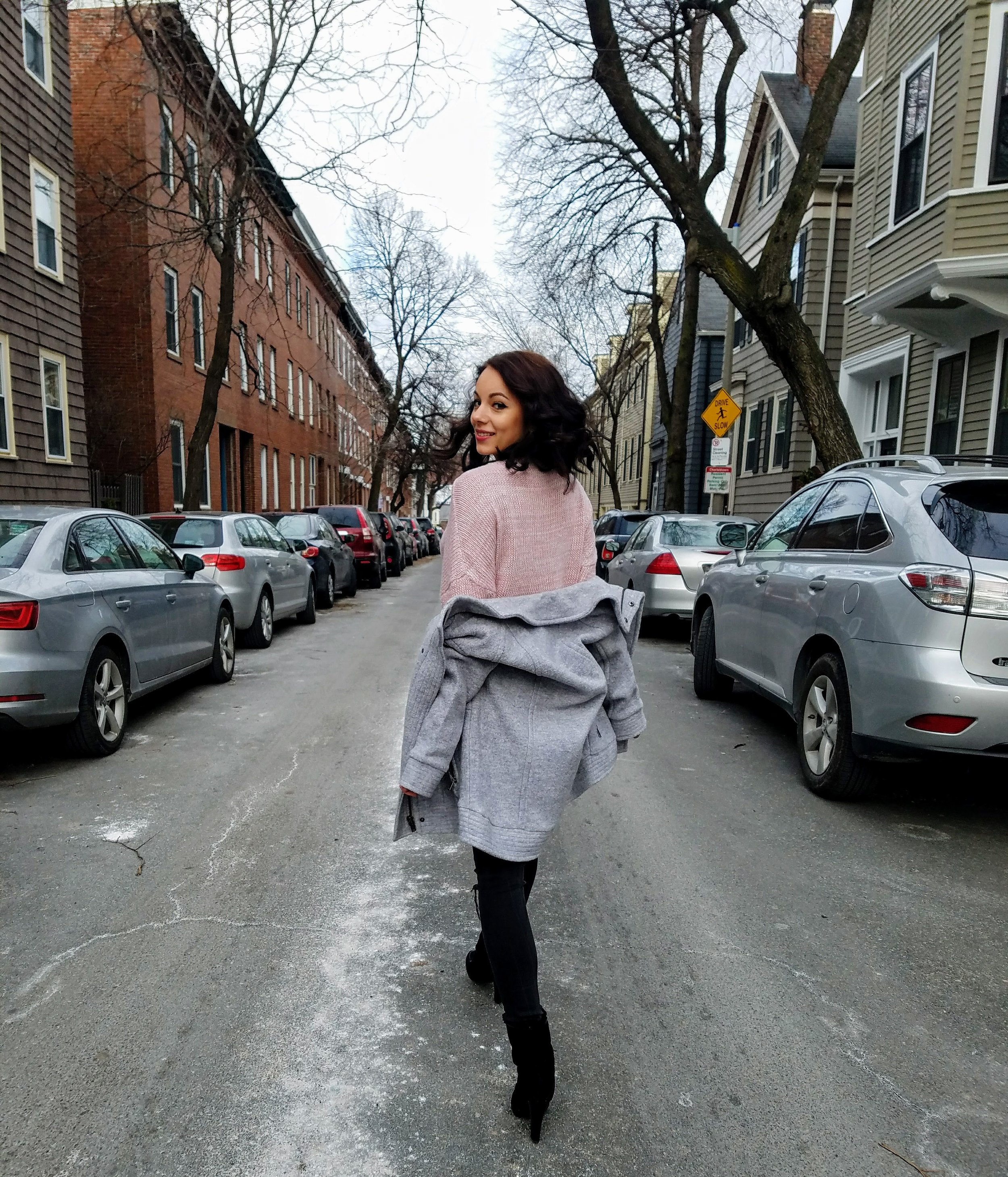A girl in Boston. Blogger. Pink sweater, gray jacket, ripped jeans, and black booties. Valentine's day.