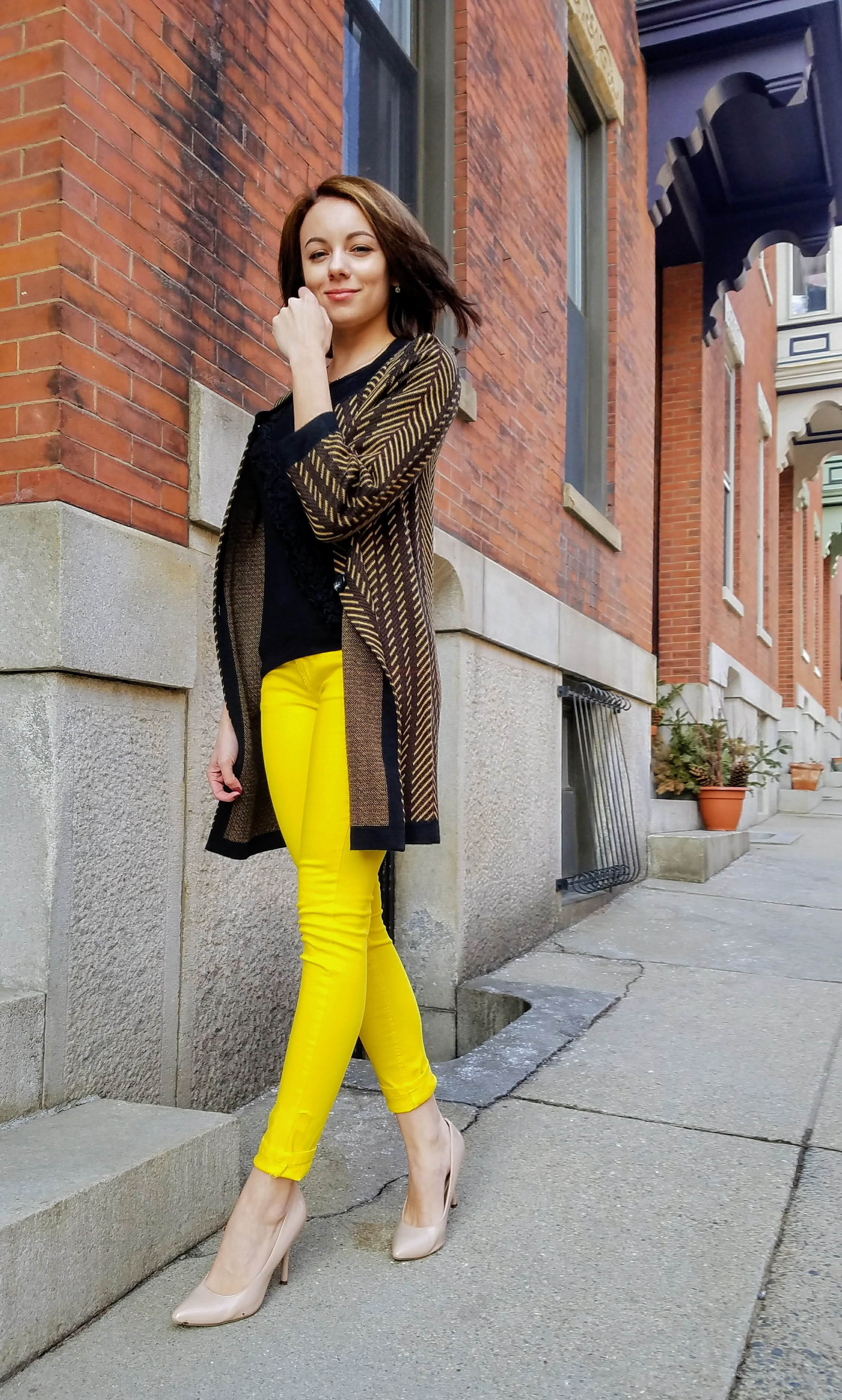 Girl in yellow pants outfit walking down sidewalk for her blog