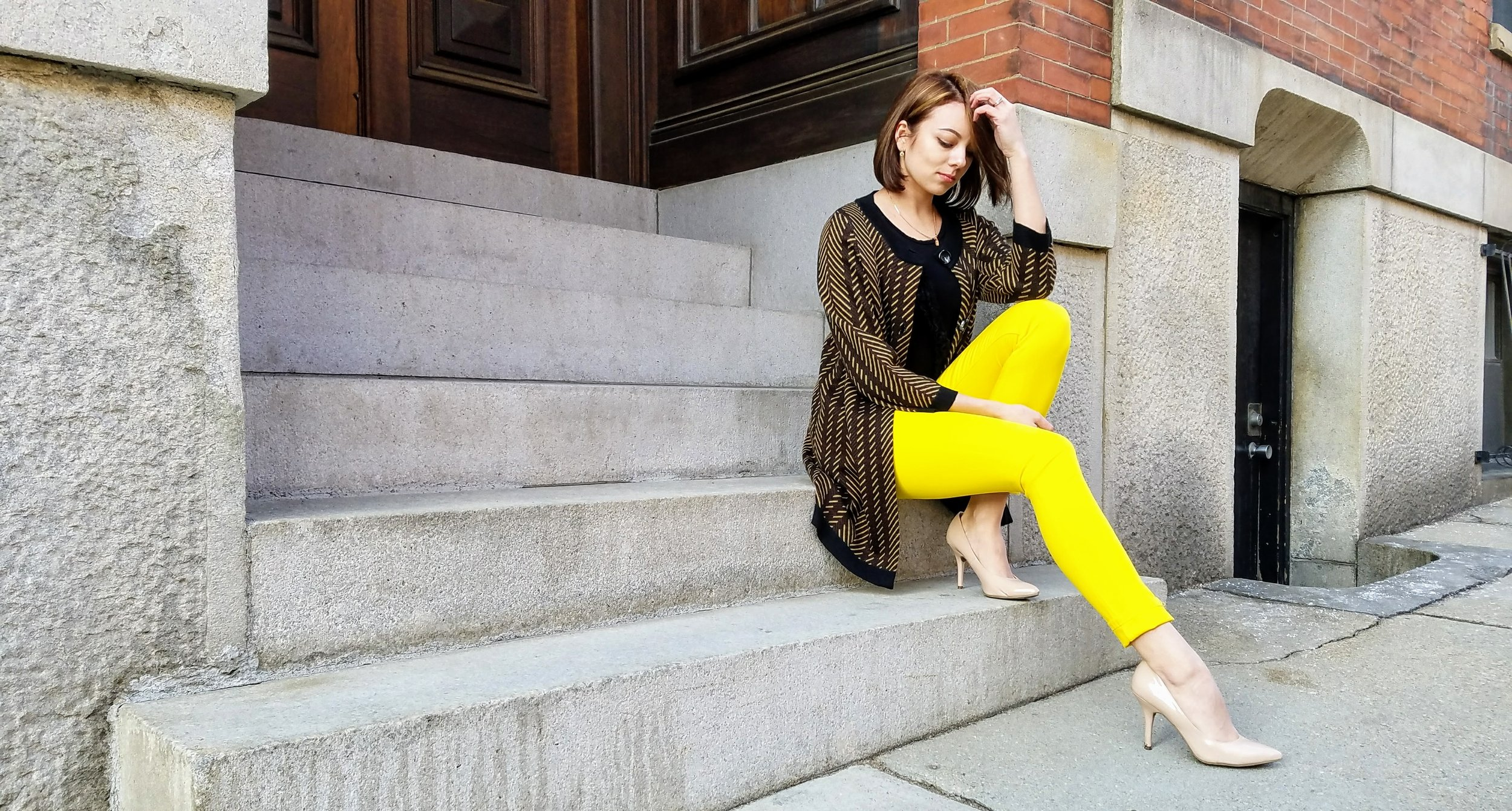 A girl in yellow pants outfit sitting on steps for her blog.